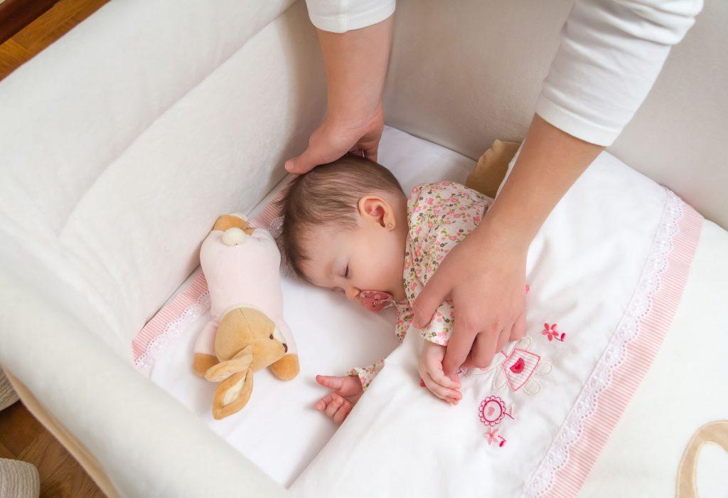 bebé dormida en cuna con mamá agarrando la mano