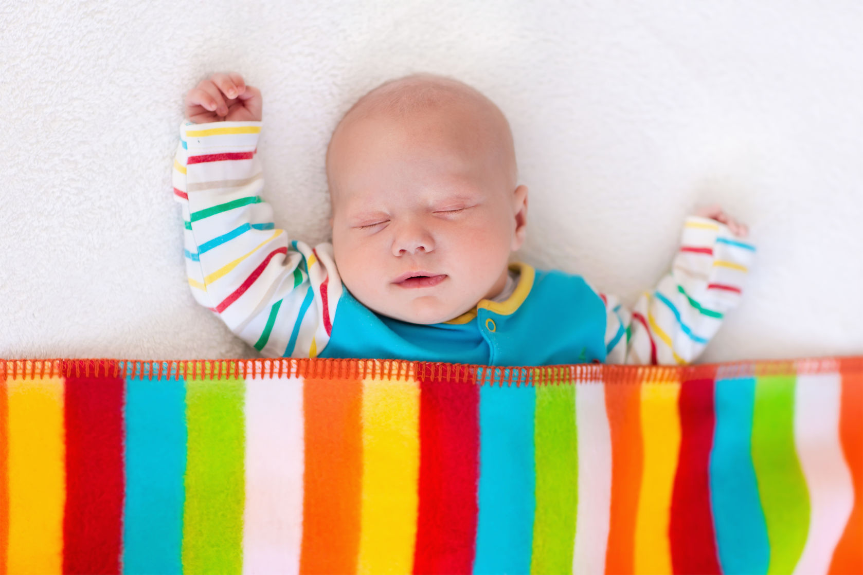 45219774 - newborn baby boy in bed. new born child sleeping under a colorful blanket. children sleep. bedding for kids. infant napping in bed. healthy little kid shortly after birth. clothing for kids.
