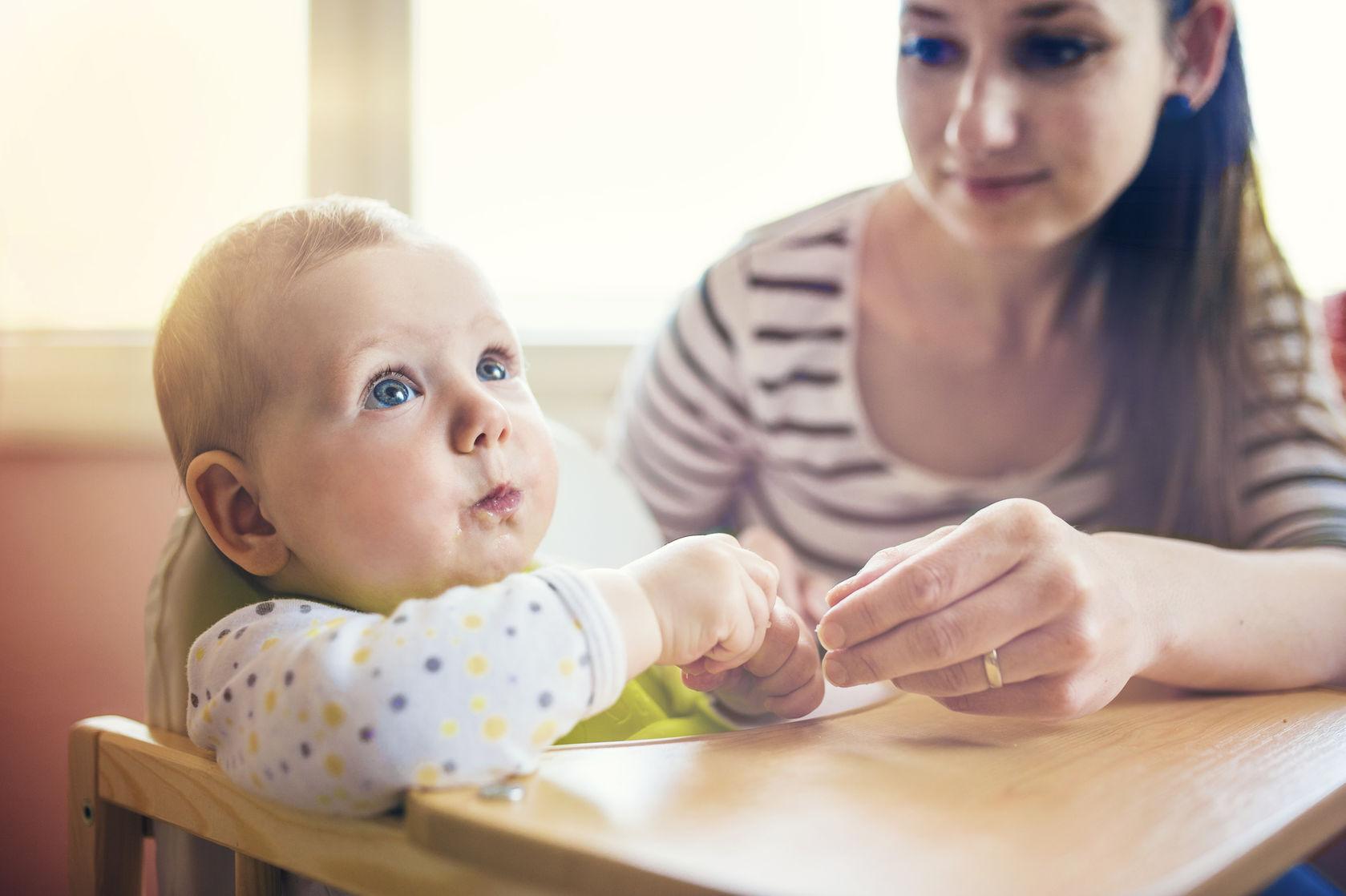 mamá dando de comer al bebé en una trona